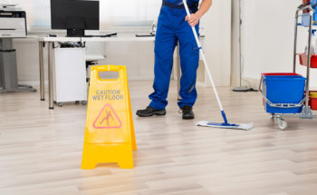 male-janitor-cleaning-floor-with-mop-in-office
